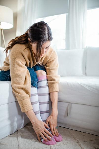 woman putting on motif compression socks